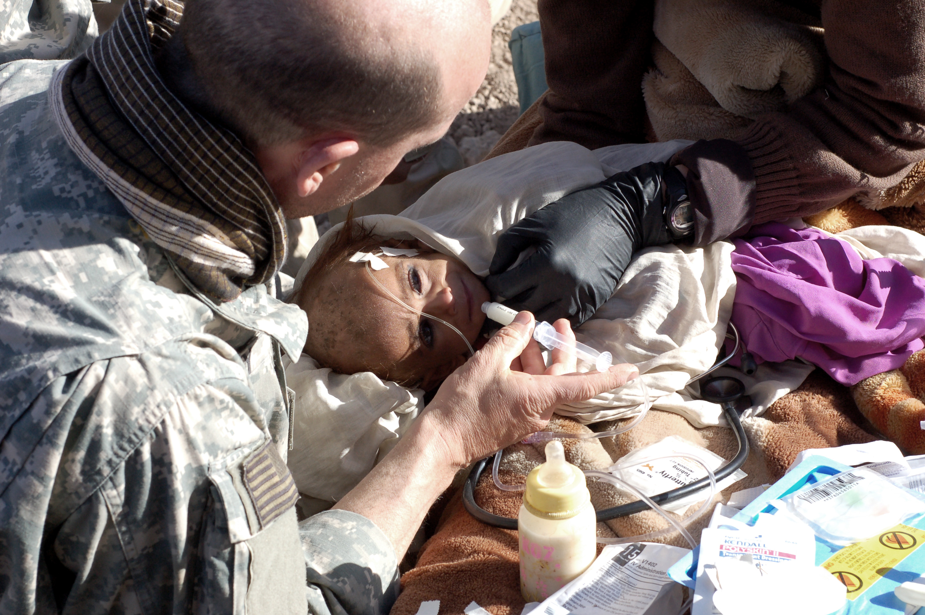 A U.S. Army medic tries to feed an 18-month gold Afghan girl using a syringe. She weighs approximately 14 pounds and is too weak to eat.